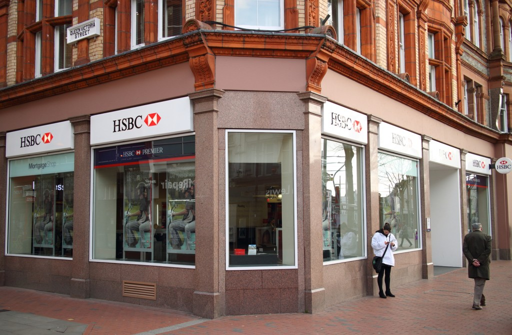 Reading, England - March 6, 2015: People in front of the HSBC Bank in Reading, England. The Hong Kong and Shanghai Banking Corporation was founded in 1865 to finance trade between Asia and the West